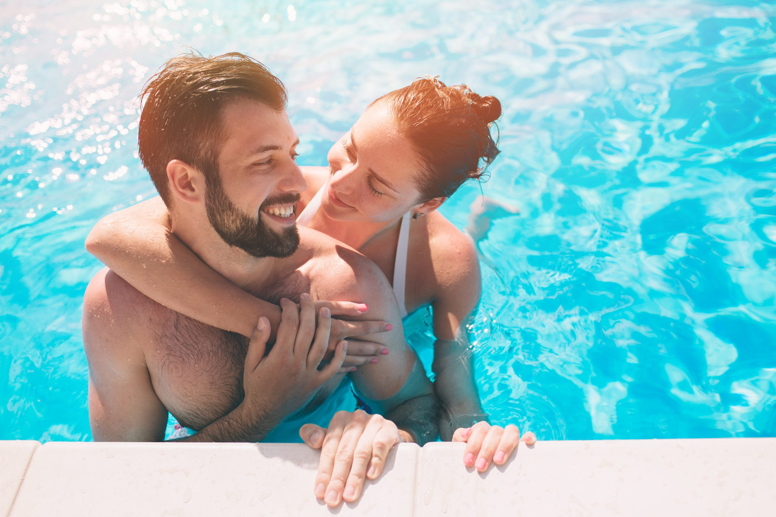 Cheerful youthful guy and lady resting while swimming pool outdoor. Couple in water.