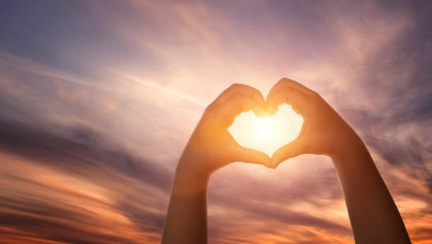 Close up of child hands formig heart shape over beautiful sky with copy space